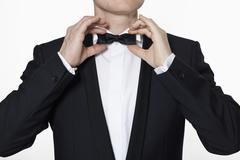 A man wearing a tuxedo adjusting his bow tie - stock photo
