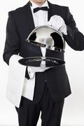 A butler taking the domed lid off an empty silver tray Stock Photos
