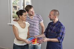 A couple consulting with a house painter, home interior Stock Photos