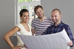 A building contractor showing blueprints to a young couple Stock Photos