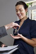 A real estate agent giving a woman the keys to her new home Stock Photos