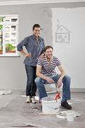 Stock Photo of A young man and woman renovating an apartment