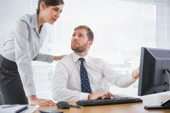 Businessman showing his co worker something on computer Stock Photos