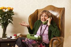 Stock Photo of A senior woman talking on the phone in her living room