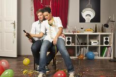 A tipsy woman sitting on her boyfriend's lap - stock photo