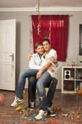 A tipsy woman sitting on her boyfriend's lap Stock Photos