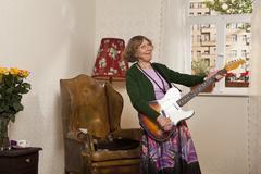 A senior woman playing an electric guitar Stock Photos
