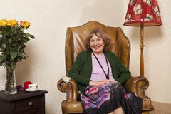 A senior woman sitting in an armchair in her living room - stock photo