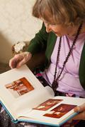 A senior woman looking through a photo album - stock photo