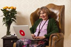 A senior woman relaxing with a laptop Stock Photos