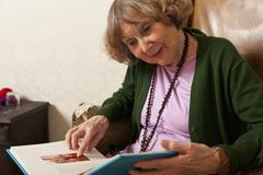 A senior woman pointing at a photograph in a photo album - stock photo