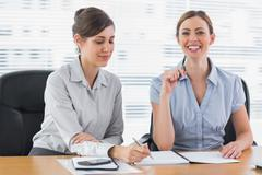 Stock Photo of Smiling businesswomen working on documents