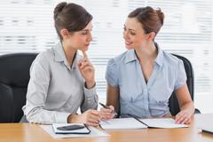 Stock Photo of Smiling businesswomen working together on documents