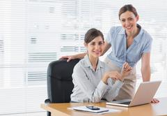 Stock Photo of Businesswomen at desk smiling at camera
