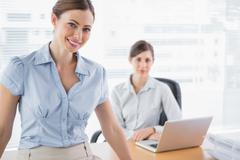 Stock Photo of Businesswomen smiling at camera at their desk