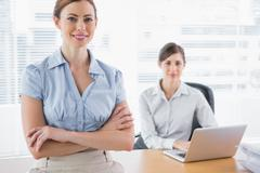 Stock Photo of Happy businesswomen smiling at camera at their desk