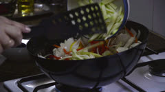 Placing zucchini to frying chicken - stock footage