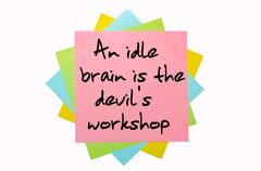 "Proverb ""an idle brain is the devil's workshop"" written on bunch of sticky no Stock Photos"