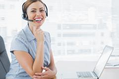 Stock Photo of Laughing call centre agent wearing headset at her desk