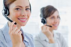 Smiling call centre agents with headsets at work - stock photo