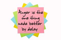 "proverb ""anger is the one thing made better by delay"" written on bunch of sti - stock photo"