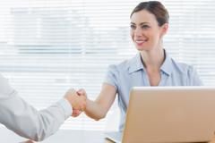 Businesswoman shaking hands with colleague - stock photo