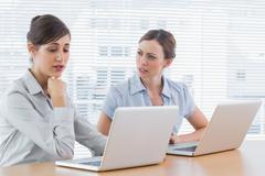 Worried businesswomen working on laptops - stock photo