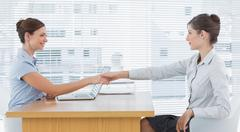 Businesswoman shaking hands with interviewee Stock Photos
