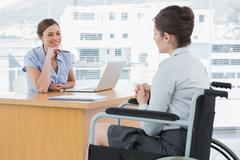 Businesswoman listening to disabled job candidate - stock photo