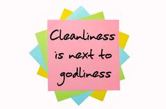 "proverb ""cleanliness is next to godliness"" written on bunch of sticky notes - stock photo"