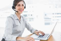 Stock Photo of Smiling call centre agent working at desk