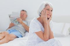 Anxious mature woman sitting on bed Stock Photos