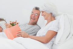 Stock Photo of Woman showing her book to her husband