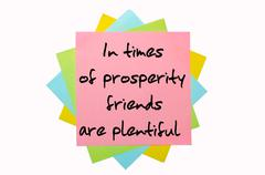 "proverb "" in times of prosperity friends are plentiful "" written on bunch of  - stock photo"