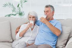 Couple drinking glasses of milk sitting on the couch - stock photo