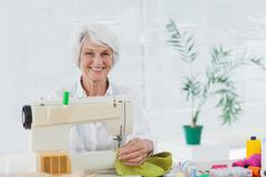 Cheerful woman using the sewing machine at home - stock photo