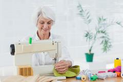 Retired woman using the sewing machine - stock photo