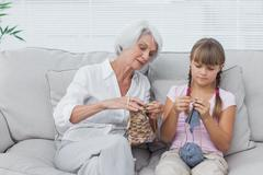 Grandmother teaching granddaughter how to knit Stock Photos