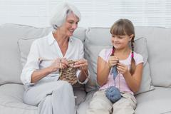 Granddaughter learning how to knit with grandmother - stock photo
