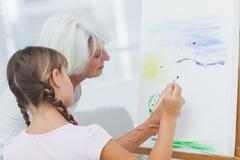 Stock Photo of Grandmother teaching granddaughter how to paint