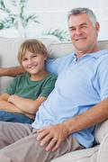 Portrait of grandson and grandfather sitting on the couch - stock photo