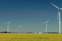 Driving by a windmill farm in a wheat field in the Midwest Stock Footage