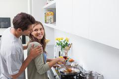 Smiling man looking at his wife who is cooking vegetables - stock photo
