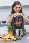 Woman leaning on her blender Stock Photos