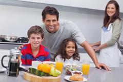 Happy family having breakfast Stock Photos