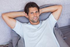 Stock Photo of Handsome man lying down in his bed
