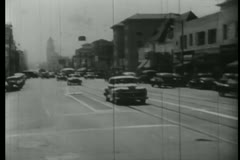 Car turning down street in downtown Los Angeles, 1940s Stock Footage
