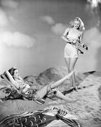 TWO WOMEN WEARING BATHING SUITS, RELAXING AT THE BEACH Stock Photos