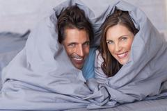 Stock Photo of Smiling couple having fun wrapped in their duvet