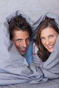 Delighted couple having fun wrapped in their duvet - stock photo